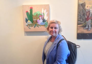Allison Bamcat posed in front of one of her gallery pieces