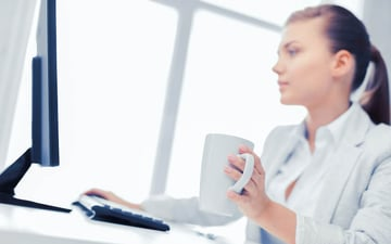Woman on a computer holding a cup of coffee