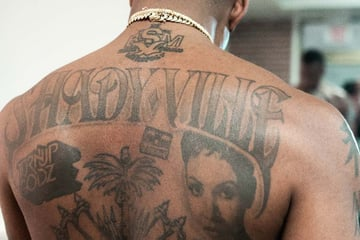 chicano lettering tattoo on the back