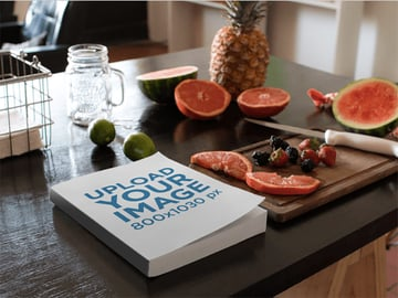 Book Lying on a Kitchen Table Next to Fruits and Knife Mockup