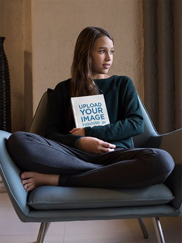 Girl Holding a Book Mockup Sitting on an Armchair
