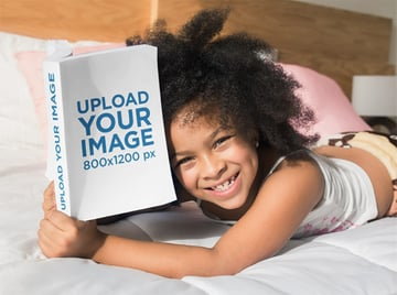 Mockup of a Smiling Girl Reading a Book on her Bed