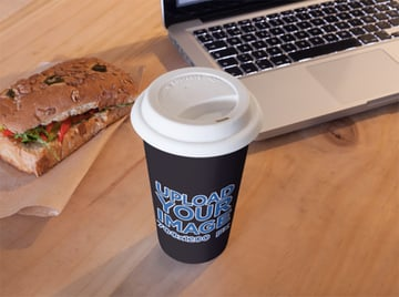 Coffee Cup Mockup Sitting Next to a Sandwich and a Macbook Pro
