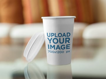 Takeaway Coffee Cup on Top of a Glass Coffee Table Label Mockup