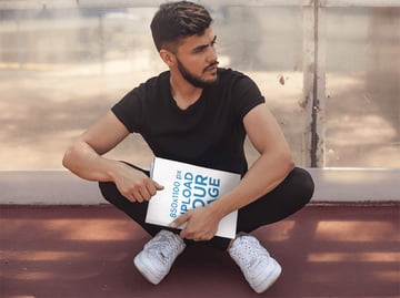 Young Hispanic Man Wearing Black Clothes While Holding a Magazine Sitting Down on the Floor Template
