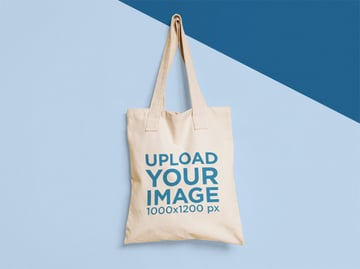 Tote Bag Mockup Hanging from a Nail on a Two Colors Wall