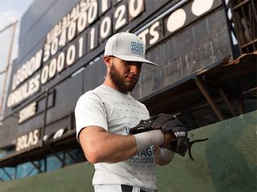 Man Wearing a Baseball Hat and a Raglan T-Shirt Mockup While Looking at his Glove Against a Board