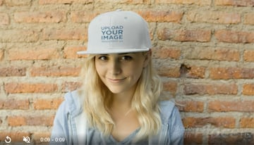 Young Woman Wearing a Snapback Hat Video Mockup Standing Against a Bricks Wall