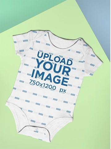 Mockup of a Baby Onesie Lying in a Colored Setting