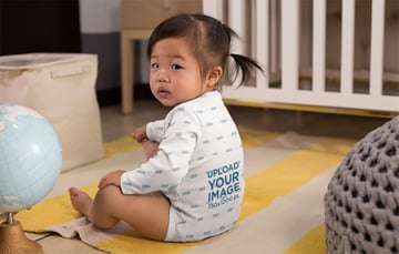 Onesie Mockup Featuring a Baby Girl by a Crib