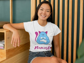 Mockup of a Woman with a Heather T-Shirt Sitting Against a Wooden Background