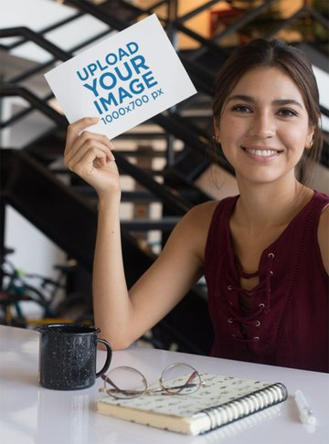Mockup of a Smiling Woman at a Table Holding an A5 Flyer