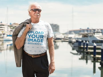 T-Shirt Mockup of a Man Standing on a Deck at the Marina
