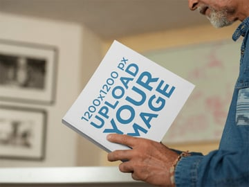 Mockup of a Man Reading a Square Book