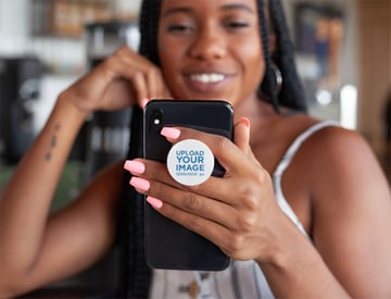 Blank Phone Grip Mockup Featuring a Smiling Woman Looking at Her iPhone