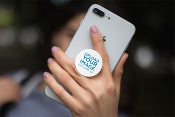 Mockup Featuring a Woman's Hand Holding a Silver iPhone 8 with a Cell Phone Grip