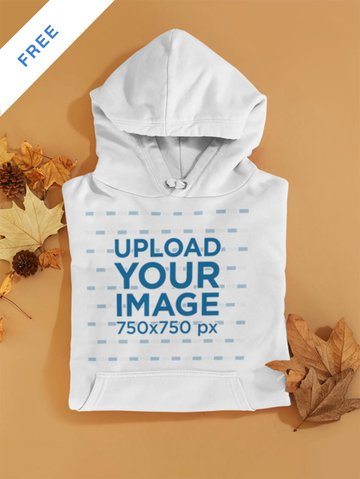 Mockup of a Folded Pullover Hoodie Placed Over Autumn Leaves