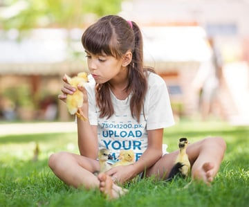 Youth T-Shirt Mockup Featuring a Girl Playing with Ducklings