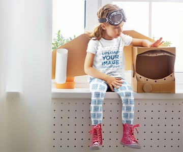 Child Shirt Mockup of a Girl with Leggings Playing with a Cardboard Astronaut Helmet