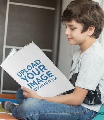 Smiling Boy Reading a Paperback Book Mockup on his Bed
