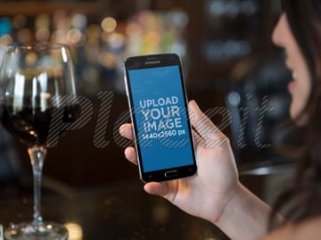 Samsung Galaxy Mockup of Woman Holding Galaxy S5 While Drinking Wine