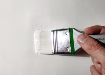 applying gesso to the blank canvas