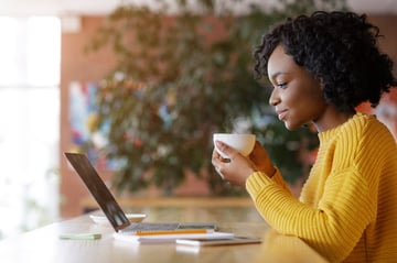 Black lady enjoying morning coffee and checking emails