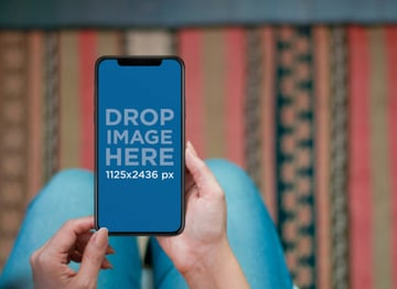Woman Using an iPhone X Mockup in her Living Room