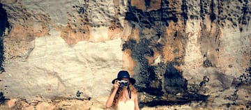 Woman in a hat with a camera standing in front of multi-colored and highly texxtured stone