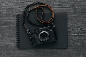 Black camera on black journal on black wooden desk
