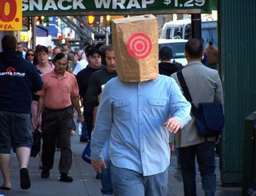 Man walking with a paper bag on his head