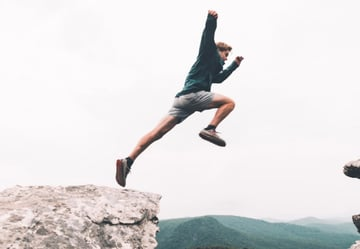 Person jumping across a gorge mountains in the distance overcast sky