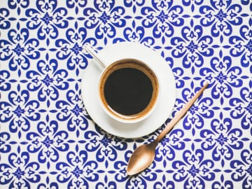 Cup of black coffee Turkish style on a patterned blue and white background