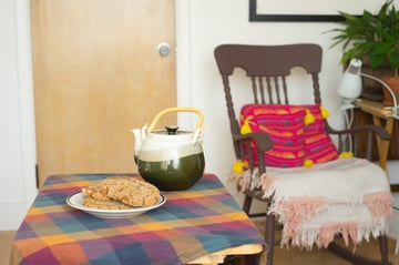 wide angle view of tea an cookies and a rocking chair