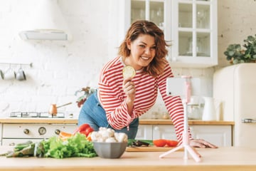 Woman food blogger demonstates on video in the kitchen