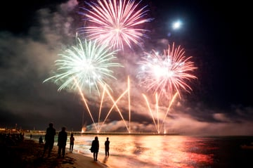 Fireworks in the night sky launched from a pier in the water across the beach