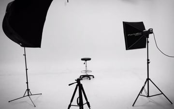 chair lighting and camera equipement in photo studio with seamless white backdrop