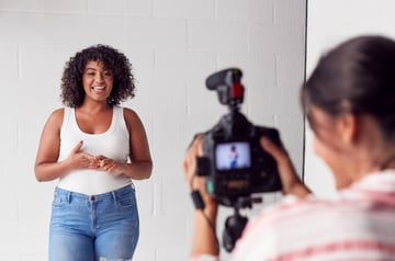 Two women recording a video in a white-walled studio