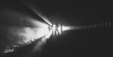 Four people in a film crew working in a dark tunnell