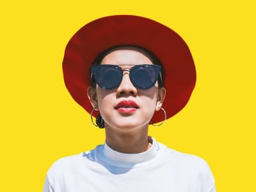 Portrait of a person in red summer hat and sunglasses over colorful yellow background summer vacation