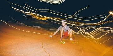Long-exposure night photograph of a skateboarders riding low to the ground