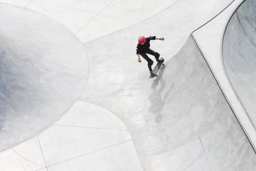 Skateboarder in a red helmet in a bowl, view from above