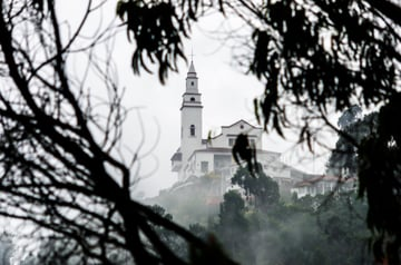 Monserrate church and cable car shrouded in mist view partially obscured by branches