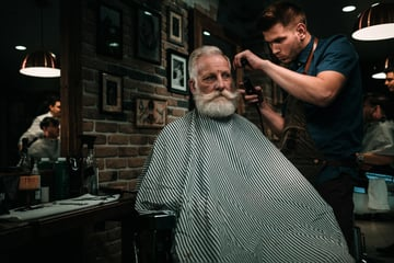 Senior man visiting hairstylist in barber shop