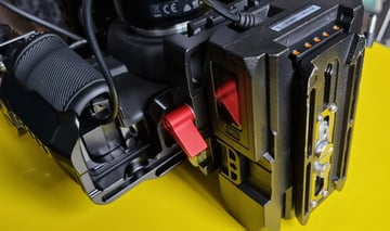 A V-Lock battery attached to the Blackmagic Pocket Cinema Camera 4K with a quick release plate underneath