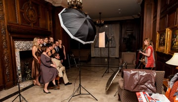 Photographer using a hotel sitting room to take a group photo