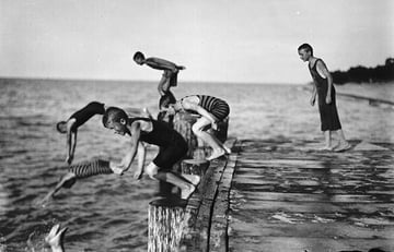 Several boys diving off a pier into water