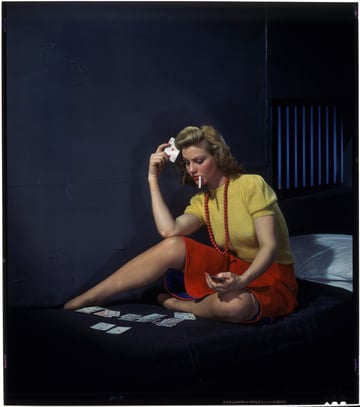 1950s woman dressed in skirt sweater and jewellery sitting on a cot in a prison cell playing cards