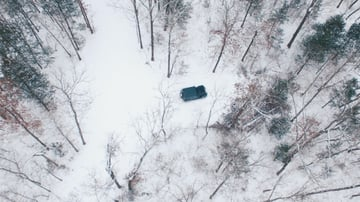 Aerial photograph of a truck in a snowy forest