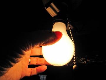 Hand changing a tungsten lightbulb